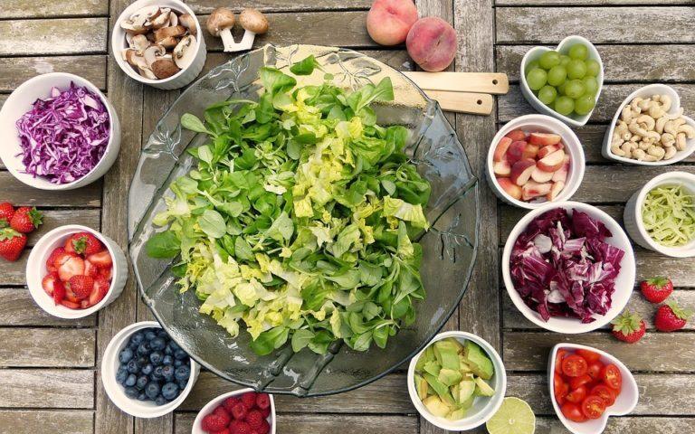Salaterka z sałatką, wokół niej miseczki z dodatkami, m. in.: cebulą, pomidorkami, oliwkami.