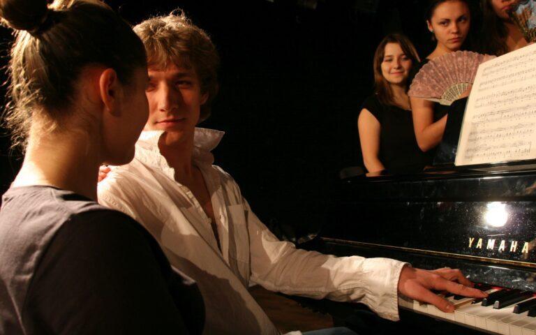 Zdjęcie, chłopak i dziewczyna przy fortepianie, chłopak patrzy na dziewczynę