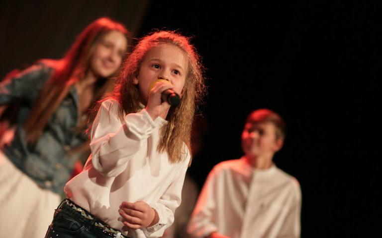 Zdjęcie, dwie dziewczyny i chłopak na scenie. Dziewczyna na pierwszym planie trzyma w dłoni mikrofon