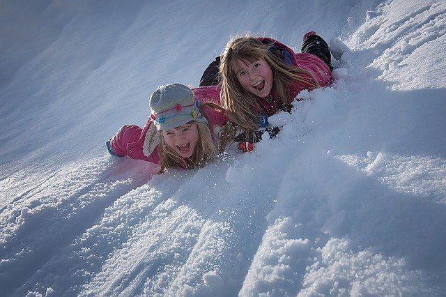 Zdjęcie, dwie dzieczynki leżą na brzuchach na śniegu