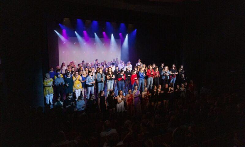 Zdjęcie - bardzo duża grupa osób ustawionych na scenie i przed nią: dzieci, młodzież, dorośli, seniorzy