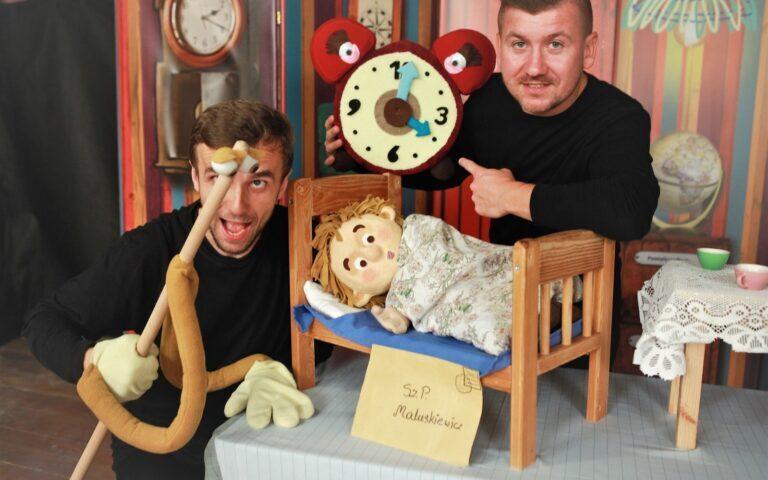 Dwóch mężczyzn w bajkowej scenografii. Między nimi małe łóżeczko, w nim kukiełka.