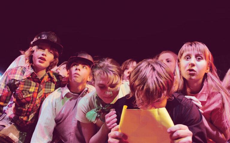 Grupa dziewcząt i chłopców stłoczonych na scenie. Chłopak w środku pochyla się nad kartką, którą trzyma w obu dłoniach.