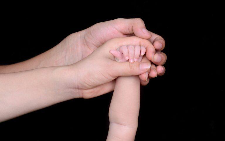 3 dłonie jedna w drugiej: mężczyzny, kobiety, dziecka.