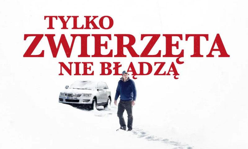 Afisz filmowy. Tytuł: Tylko zwierzęta nie błądzą. Na pierwszym planie mężczyzna stojacy na śniegu. W tle samochód osobowy.