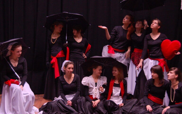 Grupa młodych dziewcząt w kostiumach pozuje do zdjęcia, kilka trzyma w dłoniach rozłożone parasole, jedna poduszkę w kształcie serca