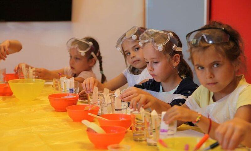 dzieci z przygotowanymi zestawami do eksperymentów: miseczki, próbki