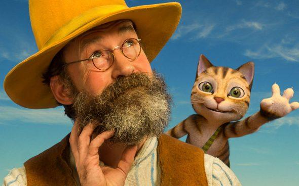 Mężczyzna z brodą w kapeluszu z kotem na ramieniu.
