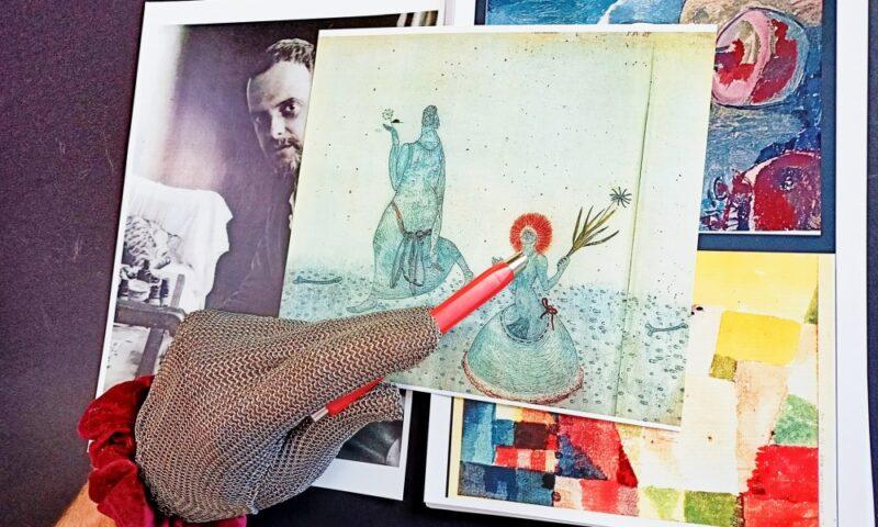 Ręka w srebrnej rękawicy wskazująca obraz Paula Klee