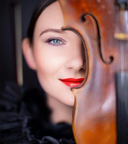 Artystka ze skrzypcami przysłaniającymi połowę twarzy.