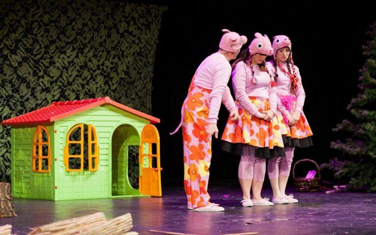 Trzy postacie w kostiumach świnek, za nimi mały domek.