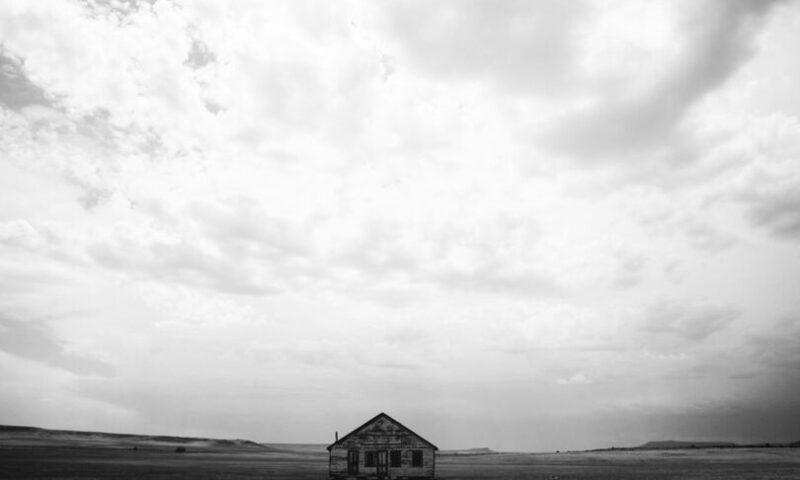 Czarno-białe zdjęcie z chatą pośrodku